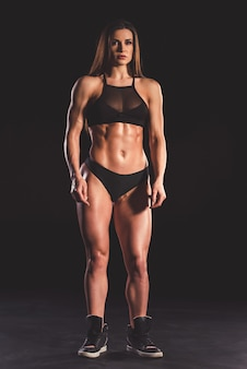 Retrato de cuerpo entero de hermosa mujer musculosa fuerte.