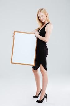Retrato de cuerpo entero de una hermosa mujer sonriente sosteniendo tablero en blanco y mirando a cámara aislada sobre fondo blanco