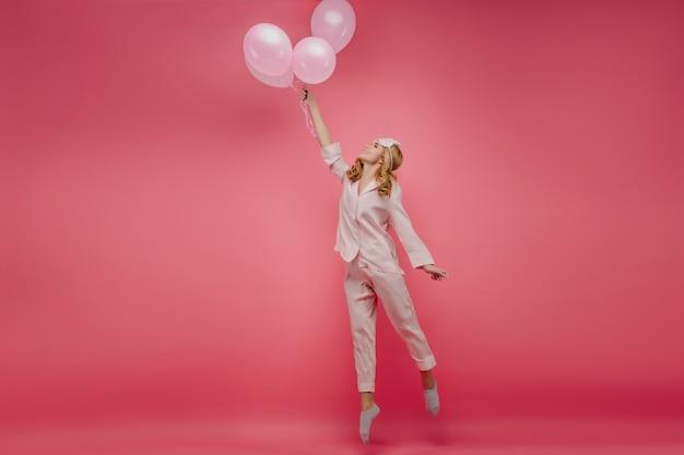 Retrato de cuerpo entero de una hermosa niña despreocupada de pie de puntillas con globos. foto interior de dama rizada en ropa de dormir rosa y antifaz saltando con una sonrisa.