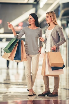 Retrato de cuerpo entero de hermosas chicas con bolsas de compras.