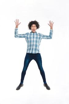 Retrato de cuerpo entero de un hombre afroamericano divertido saltando aislado en una pared blanca