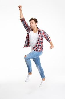 Retrato de cuerpo entero de un hombre atractivo casual saltando