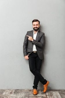 Retrato de cuerpo entero de hombre atractivo posando en la cámara con una amplia sonrisa apuntando el dedo índice a un lado, aislado en gris