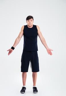 Retrato de cuerpo entero de un hombre de deportes encogiéndose de hombros aislado