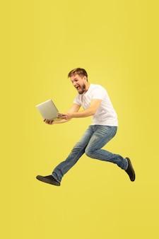 Retrato de cuerpo entero de hombre feliz saltando aislado sobre fondo amarillo. modelo masculino caucásico en ropa casual