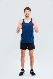 Retrato de cuerpo entero de un hombre de fitness feliz mostrando dos pulgares hacia arriba aislado sobre un fondo gris