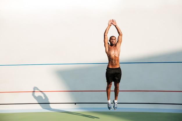 Retrato de cuerpo entero de un hombre de gimnasio africano medio desnudo saltando