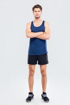 Retrato de cuerpo entero de un hombre guapo en ropa deportiva de pie con las manos cruzadas aislado sobre un fondo gris y mirando a la cámara