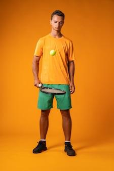 Retrato de cuerpo entero de un hombre jugador de tenis en acción contra el fondo naranja de cerca