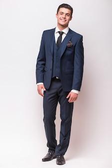 Retrato de cuerpo entero de un hombre de negocios en traje de pie sobre una pared blanca aislada