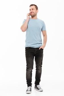 Retrato de cuerpo entero de hombre satisfecho con rastrojo de pie con la mano en el bolsillo mientras habla por teléfono móvil