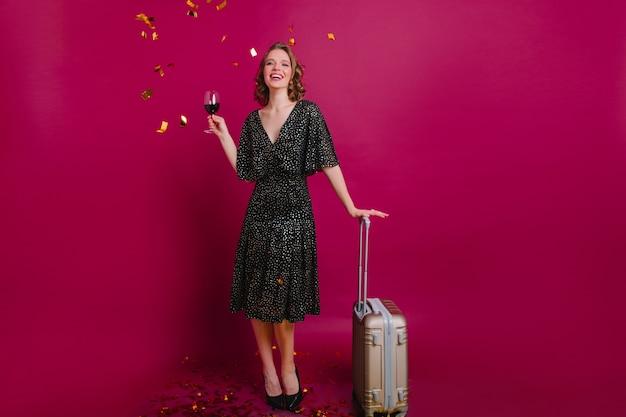Retrato de cuerpo entero de increíble modelo femenino rizado pasar tiempo antes de viajar. adorable niña caucásica bebiendo vino después de empacar ropa para vacaciones.