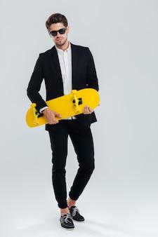 Retrato de cuerpo entero de un joven apuesto hombre de negocios en traje y gafas de sol con patineta amarilla sobre pared gris