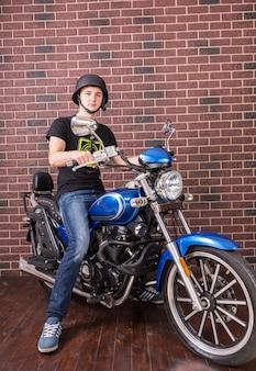 Retrato de cuerpo entero de joven con casco sentado en la motocicleta azul clásica delante de la pared de ladrillo