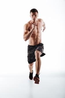 Retrato de cuerpo entero del joven corredor atractivo en movimiento