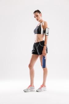 Retrato de cuerpo entero de una joven deportista agotada en auriculares
