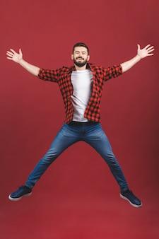 Retrato de cuerpo entero de un joven excitado saltando