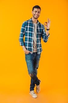 Retrato de cuerpo entero de un joven feliz con camisa a cuadros aislado sobre una pared naranja, mostrando ok