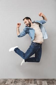 Retrato de cuerpo entero de un joven feliz con camisa saltando por encima de la pared gris, celebrando