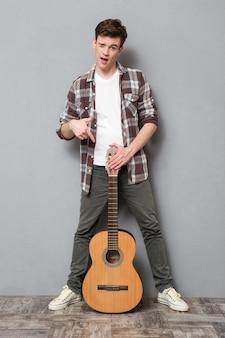 Retrato de cuerpo entero de un joven guiñando un ojo y señalando con el dedo en la guitarra en la pared gris