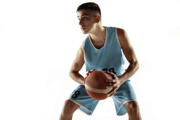 Retrato de cuerpo entero del joven jugador de baloncesto con una pelota aislada sobre fondo blanco de estudio. adolescente entrenando y practicando en acción, movimiento. concepto de deporte, movimiento, estilo de vida saludable, anuncio.