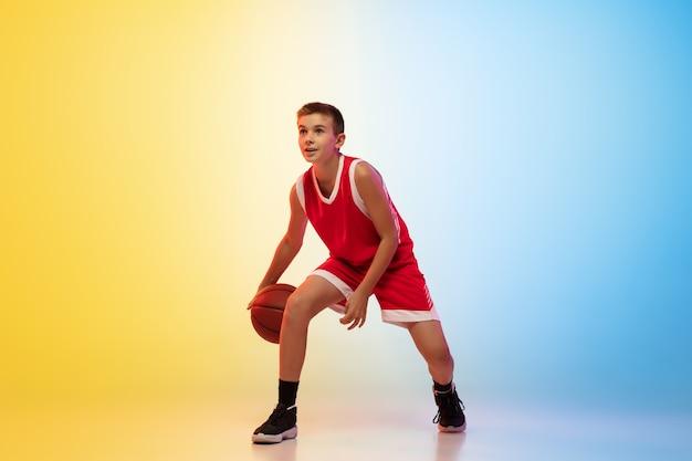 Retrato de cuerpo entero de un joven jugador de baloncesto con pelota sobre fondo degradado