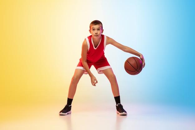 Retrato de cuerpo entero del joven jugador de baloncesto en uniforme en la pared degradada