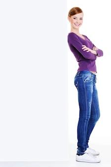 Retrato de cuerpo entero de una joven linda mujer feliz cerca de cartelera en blanco sobre espacio en blanco
