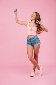 Retrato de cuerpo entero de una joven mujer sonriente de cabeza lectora en ropa de verano hace selfie en teléfono inteligente, mostrando el signo de la paz