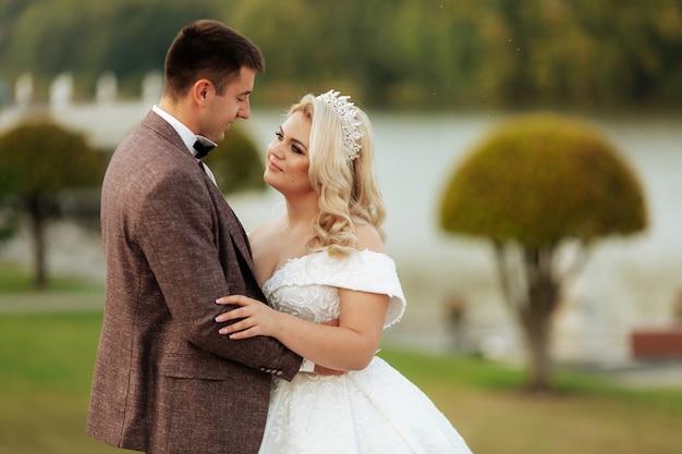 Retrato de cuerpo entero de la joven novia y el novio corriendo sobre la hierba verde del campo de golf. feliz pareja caminando por el campo de golf, espacio de copia