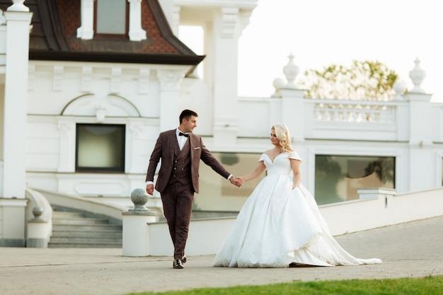 Retrato de cuerpo entero de la joven novia y el novio en el parque del castillo