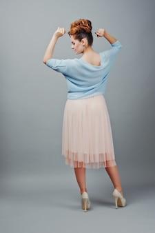 Retrato de cuerpo entero de joven pelirroja rizada en blusa azul y falda rosa