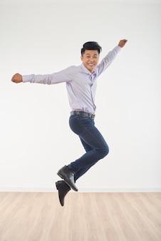 Retrato de cuerpo entero del joven saltando lleno de felicidad