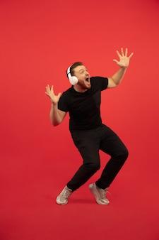 Retrato de cuerpo entero de un joven salto alto aislado en la pared roja. modelo masculino caucásico. copyspace. las emociones humanas, la expresión facial, el concepto de deporte.