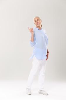 Retrato de cuerpo entero de juguetona mujer madura en camisa azul y pantalón blanco, de pie y señalando con el dedo, mirando a un lado