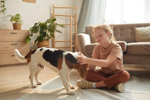 Retrato de cuerpo entero de una linda chica pelirroja jugando con el perro mientras está sentado en el suelo en el acogedor interior de una casa iluminada por la luz del sol