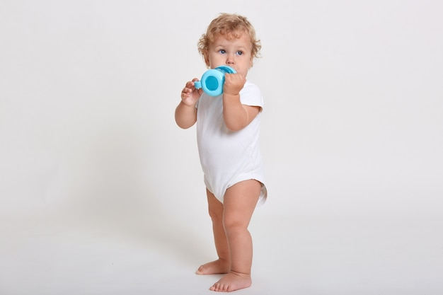 Retrato de cuerpo entero de lindo niño bebiendo agua de botella, niño de un año jugando con taza de bebé, adorable niño de pelo rizado mirando a otro lado
