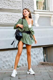 Retrato de cuerpo entero de la modelo sonriente alegre alegre joven hipster, posando en la calle, vistiendo un atuendo estilo botín de moda de los años 90.