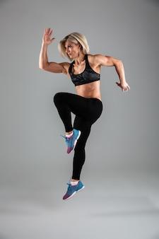 Retrato de cuerpo entero de una mujer adulta muscular fitness saltando