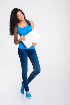 Retrato de cuerpo entero de una mujer afroamericana feliz sosteniendo portátil aislado en una pared blanca