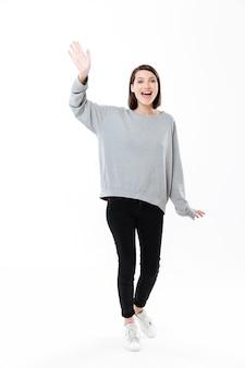 Retrato de cuerpo entero de una mujer agitando la mano