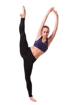 Retrato de cuerpo entero mujer atleta estirando la pierna mientras se calienta aislado sobre fondo blanco.