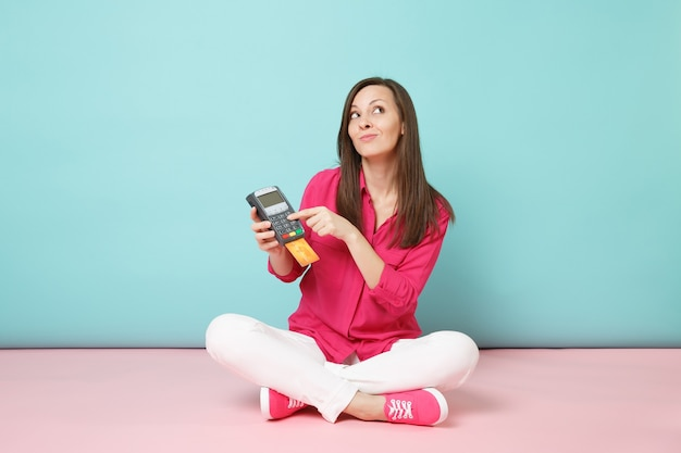Retrato de cuerpo entero de una mujer con camisa rosa, pantalón blanco sentado en el suelo, mantenga la tarjeta terminal
