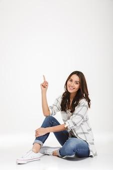 Retrato de cuerpo entero de mujer complacida en ropa casual sentada en el suelo y apuntando el dedo índice con una amplia sonrisa, aislado sobre la pared blanca
