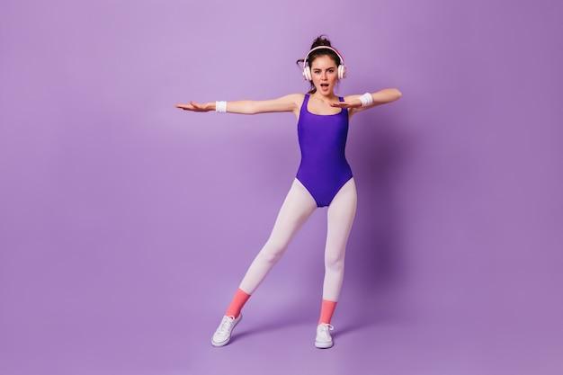 Retrato de cuerpo entero de mujer delgada en traje violeta y leggings blancos al estilo de los años 80, haciendo aeróbicos en auriculares