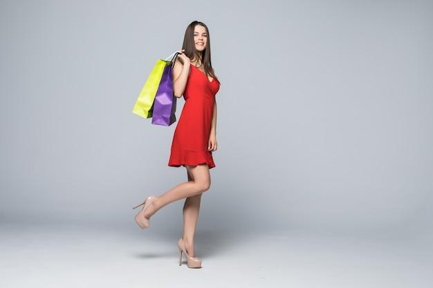 Retrato de cuerpo entero de una mujer feliz emocionada en vestido rojo de pie y sosteniendo coloridas bolsas de compras aisladas en una pared blanca