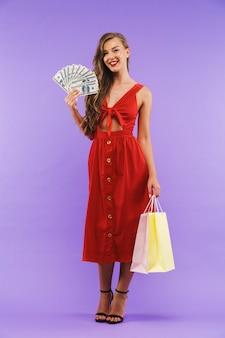 Retrato de cuerpo entero de mujer feliz vistiendo vestido rojo sonriendo sosteniendo abanico de dinero en dólares y bolsas de papel