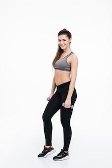 Retrato de cuerpo entero de una mujer fitness sonriente de pie y sosteniendo pequeñas pesas aisladas