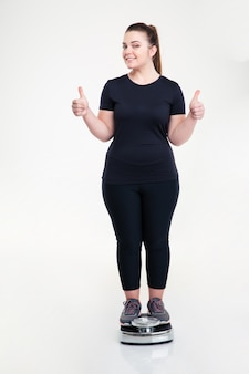 Retrato de cuerpo entero de una mujer gruesa feliz de pie en la balanza y mostrando los pulgares para arriba aislado en una pared blanca