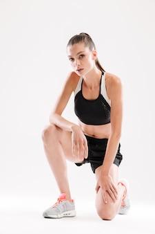 Retrato de cuerpo entero de una mujer joven agotada fitness descansando